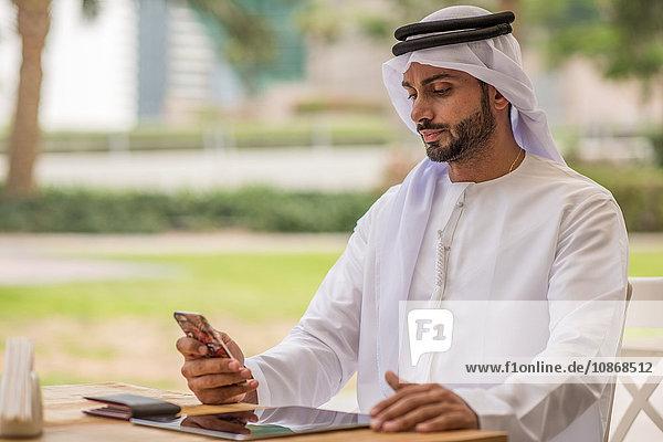 Mann aus dem Nahen Osten in traditioneller Kleidung liest Smartphone-Text im Café  Dubai  Vereinigte Arabische Emirate