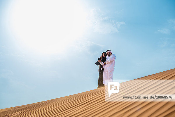Paar aus dem Nahen Osten in traditioneller Kleidung mit Smartphone-Selfie auf Wüstendüne  Dubai  Vereinigte Arabische Emirate