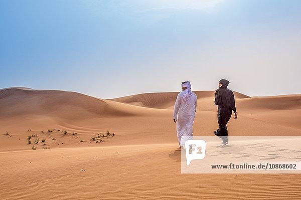 Paar in traditioneller nahöstlicher Kleidung zu Fuß in der Wüste  Dubai  Vereinigte Arabische Emirate