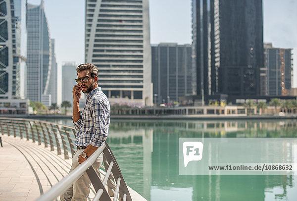 Junger Mann lehnt an Ufergeländer gelehnt und spricht über Smartphone  Dubai  Vereinigte Arabische Emirate