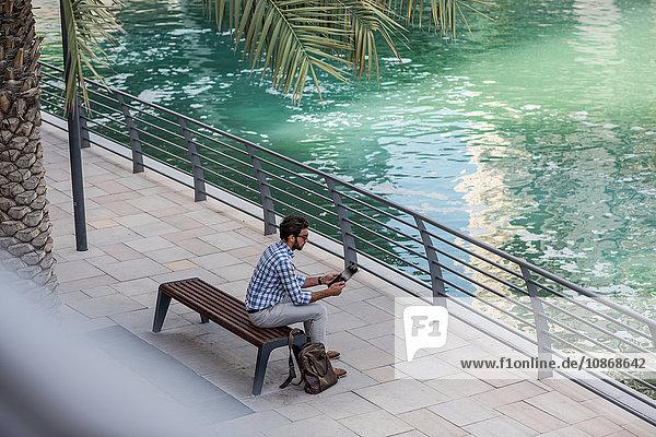 Hochwinkelansicht eines jungen Mannes  der am Wasser sitzt  mit einem digitalen Tablet  Dubai  Vereinigte Arabische Emirate