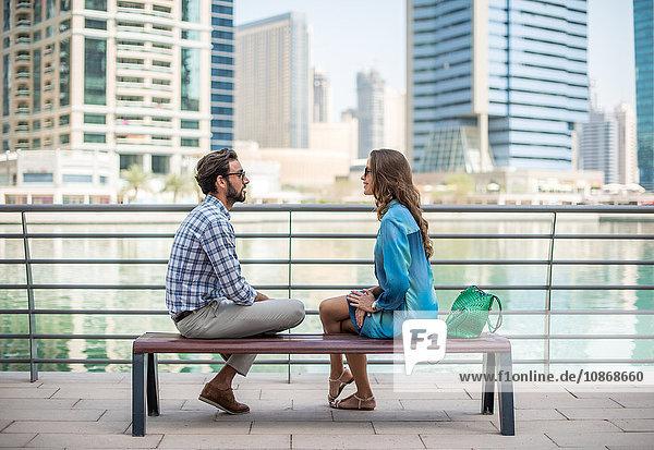 Touristenpaar sitzt am Wasser und unterhält sich  Dubai  Vereinigte Arabische Emirate