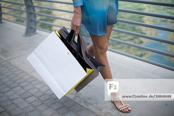 Taillenansicht einer Frau  die am Wasser mit einer Einkaufstasche spazieren geht  Dubai  Vereinigte Arabische Emirate