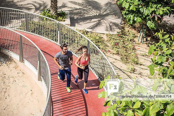 High angle view of running couple running up footbridge  Dubai  United Arab Emirates