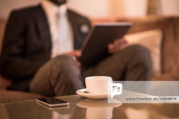 Ausschnittaufnahme eines jungen Geschäftsmannes  der auf einem Hotelsofa sitzt und ein digitales Tablet benutzt