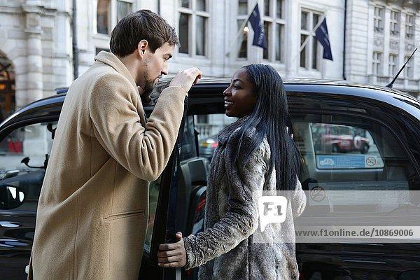 Paar im Freien  verabschiedet sich  Frau steigt ins Taxi  lächelt