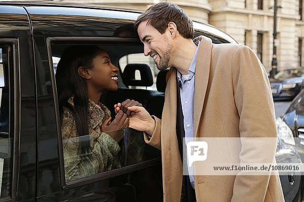 Couple saying goodbye through taxi window  holding hands  smiling