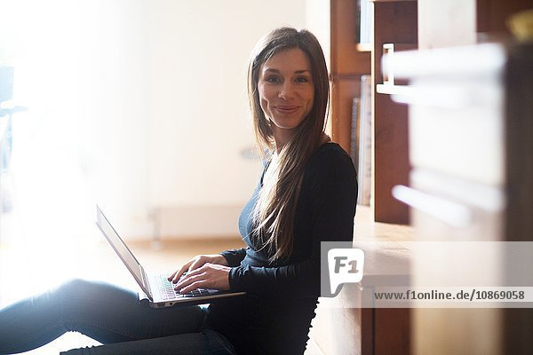 Porträt einer jungen Frau zu Hause  die einen Laptop benutzt