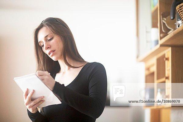 Junge Frau zu Hause  schreibt auf Notizblock
