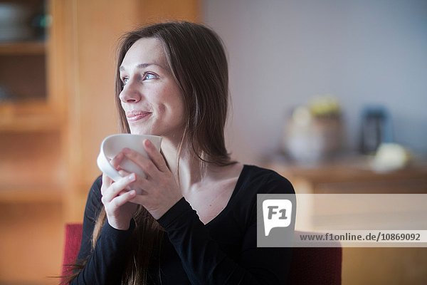 Young woman at home  holding hot drink