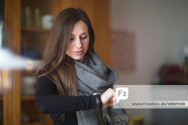 Junge Frau zu Hause  die auf die Uhr schaut