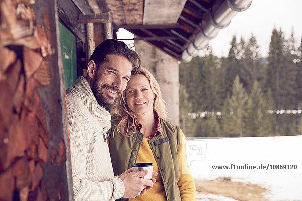 Portrait of couple standing outside log cabin in winter  Elmau  Bavaria  Germany