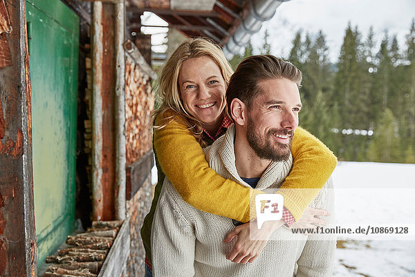 Young man giving piggyback to girlfriend outside log cabin  Elmau  Bavaria  Germany