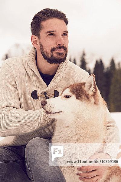 Young man petting husky in snow  Elmau  Bavaria  Germany