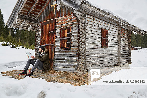 Young man reading map sitting outside log cabin in winter  Elmau  Bavaria  Germany