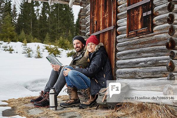 Portrait of couple reading map sitting outside log cabin in winter  Elmau  Bavaria  Germany
