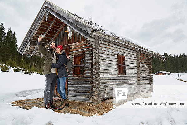 Couple taking smartphone selfie outside log cabin in winter  Elmau  Bavaria  Germany