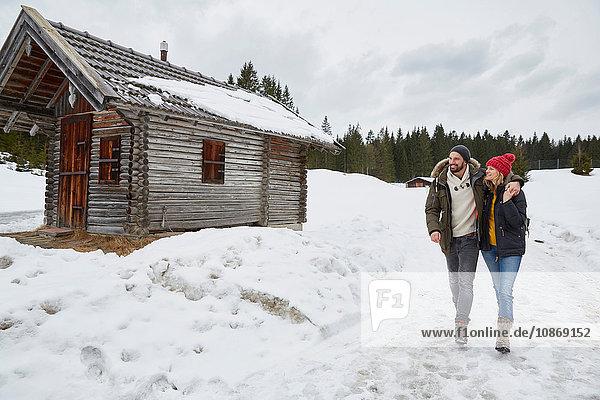 Couple hiking from log cabin in winter  Elmau  Bavaria  Germany