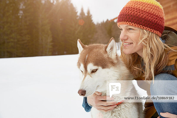 Woman kneeling with husky in snow covered landscape,  Elmau,  Bavaria,  Germany