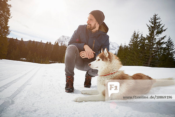 Young man crouching with husky in snow covered landscape  Elmau  Bavaria  Germany