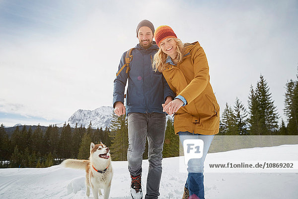 Portrait of couple walking husky in snow covered landscape  Elmau  Bavaria  Germany