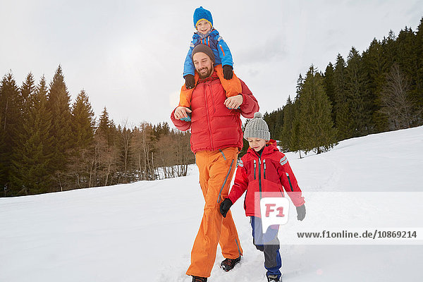 Young man shoulder carrying and walking with sons in snow covered landscape  Elmau  Bavaria  Germany