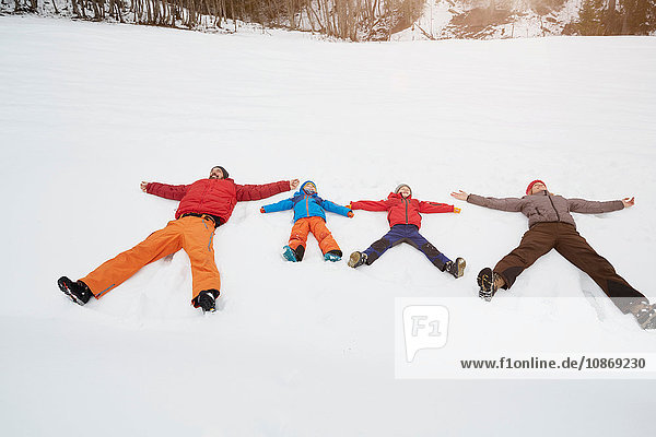 Parents and sons lying in snow covered landscape  Elmau  Bavaria  Germany