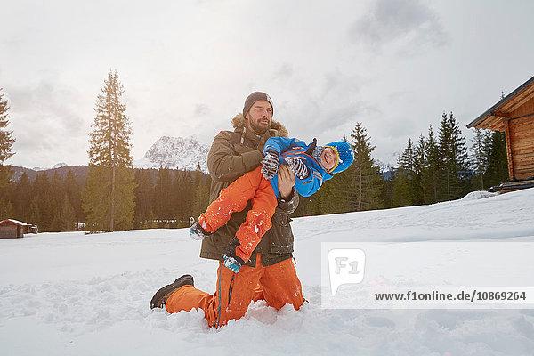Father lifting up son in snow  Elmau  Bavaria  Germany