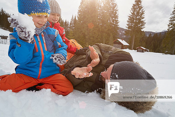 Father and sons having snowball fight in winter  Elmau  Bavaria  Germany