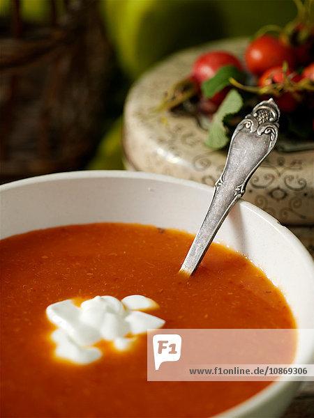 Nahaufnahme einer Schüssel mit Tomatensuppe und frischer Sahne