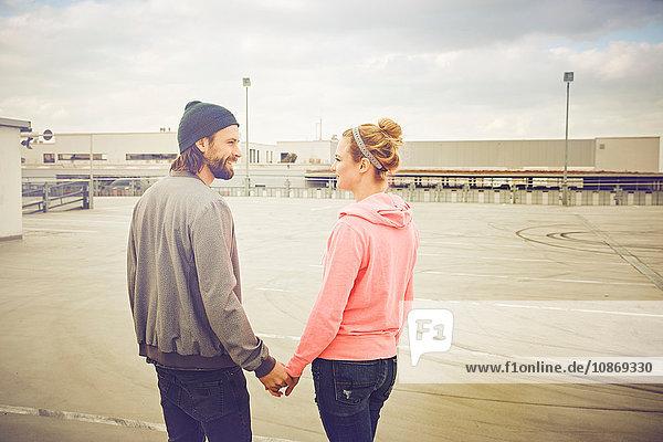 Mittelgroßes erwachsenes Paar hält sich auf dem Dachparkplatz an den Händen
