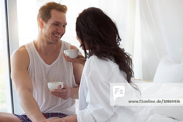 Glückliches junges Paar beim Kaffee im Bett