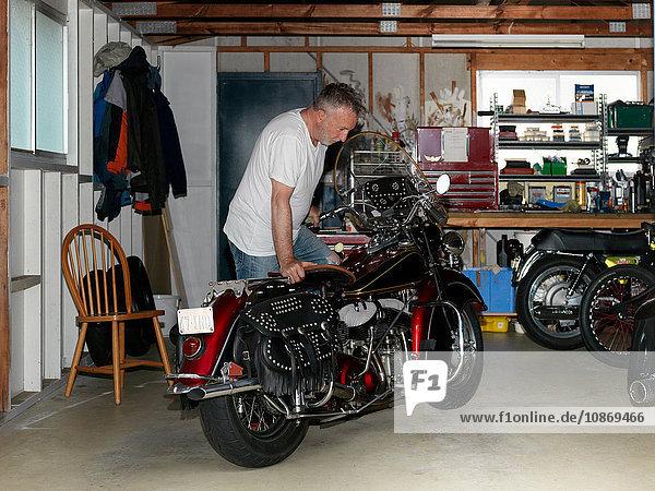 Älterer Mann kontrolliert Motorrad in Garage