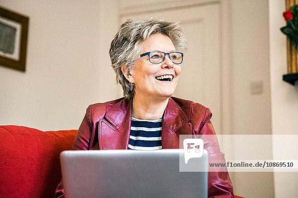 Senior woman on living room sofa using laptop