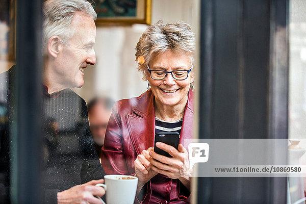 Älteres Ehepaar sitzt am Fensterplatz eines Cafés  trinkt Kaffee und simst per Smartphone
