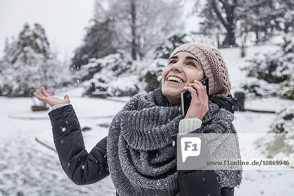 Frau in schneebedeckter Landschaft telefoniert mit Smartphone