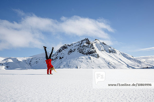 Woman doing handstand on snow-covered field  Litla-heidi  Iceland