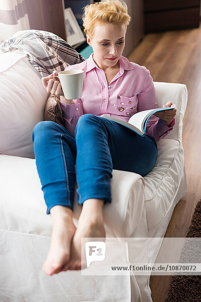 Woman reading and having coffee on sofa
