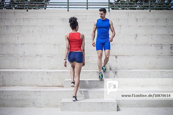 Junge Frau und Mann gehen während des Trainings auf einer Treppe vorbei