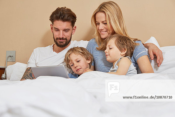 Mother and father in bed with sons looking at digital tablet