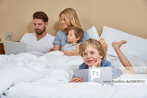 Mutter und Vater im Bett mit Söhnen mit Technologie