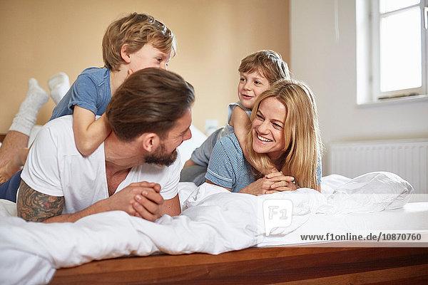 Jungen im Bett  die auf den Eltern liegen und von Angesicht zu Angesicht lächeln