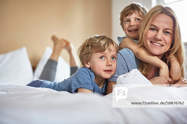 Boys on bed lying on top of mother looking at camera smiling