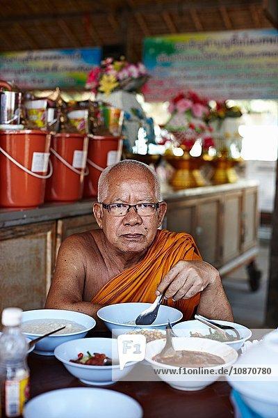 Buddhist monk eating  Damnoen Saduak Market  Thailand