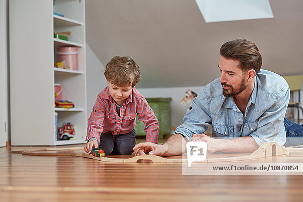 Father and son playing with wooden toy train set