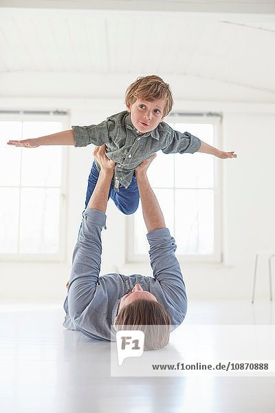Father lying on floor holding up son