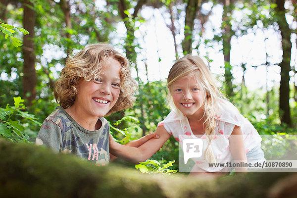 Junge und Mädchen im Wald schauen lächelnd in die Kamera Junge und Mädchen im Wald schauen lächelnd in die Kamera