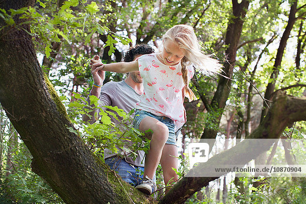 Father helping daughter to climb tree