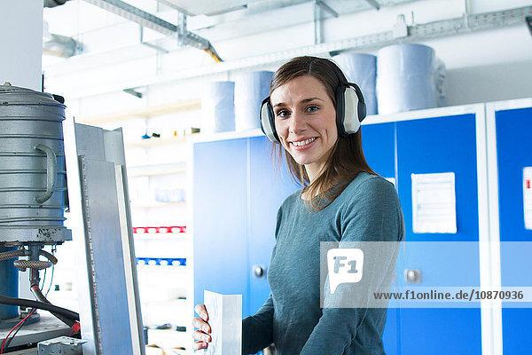 Woman in workshop wearing ear defenders looking at camera smiling