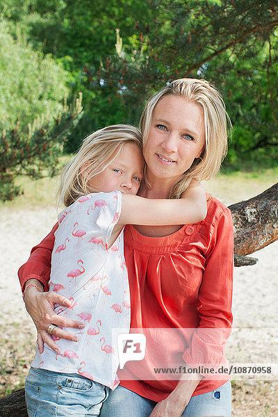 Mutter und Tochter lehnen am Baum und schauen lächelnd in die Kamera